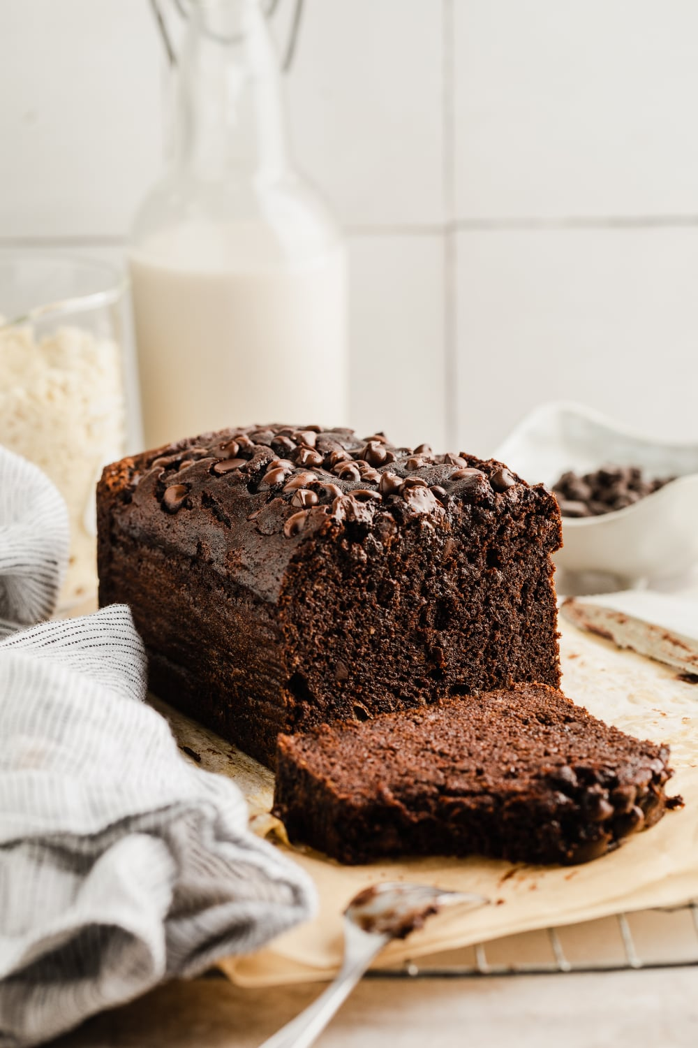 photo of a loaf of chocolate banana bread with a glass of milk