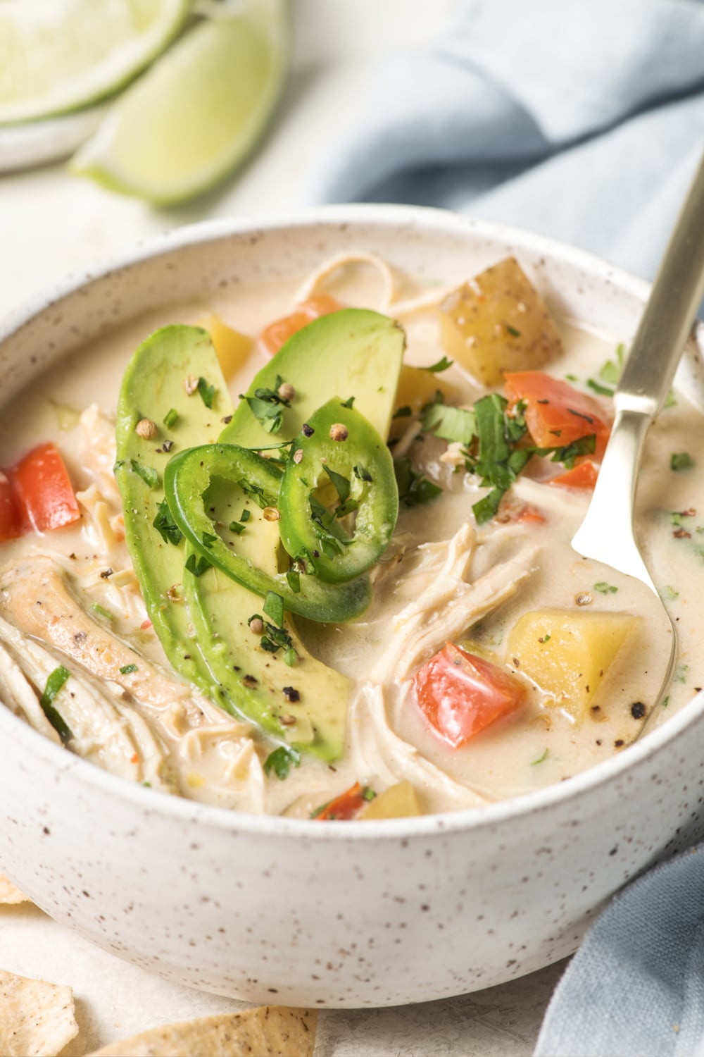 close up of paleo white chicken chili in a bowl with a spoon