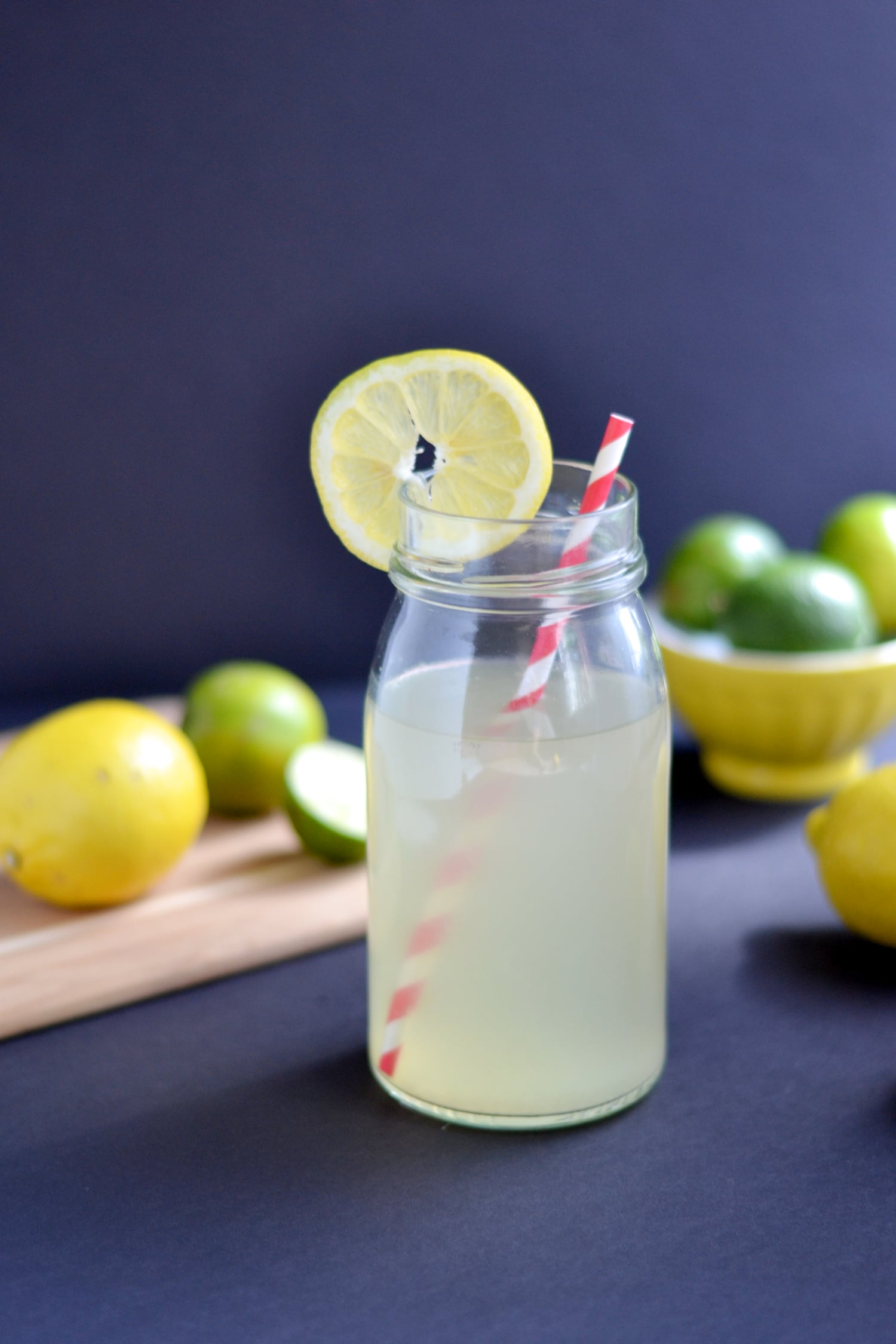glass of homemade electrolyte drink with lemons and limes around it