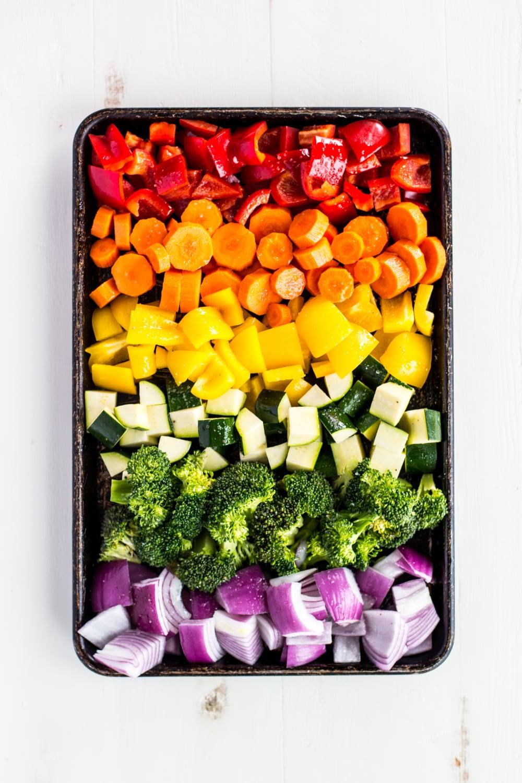 uncooked vegetables on a sheet pan seasoned