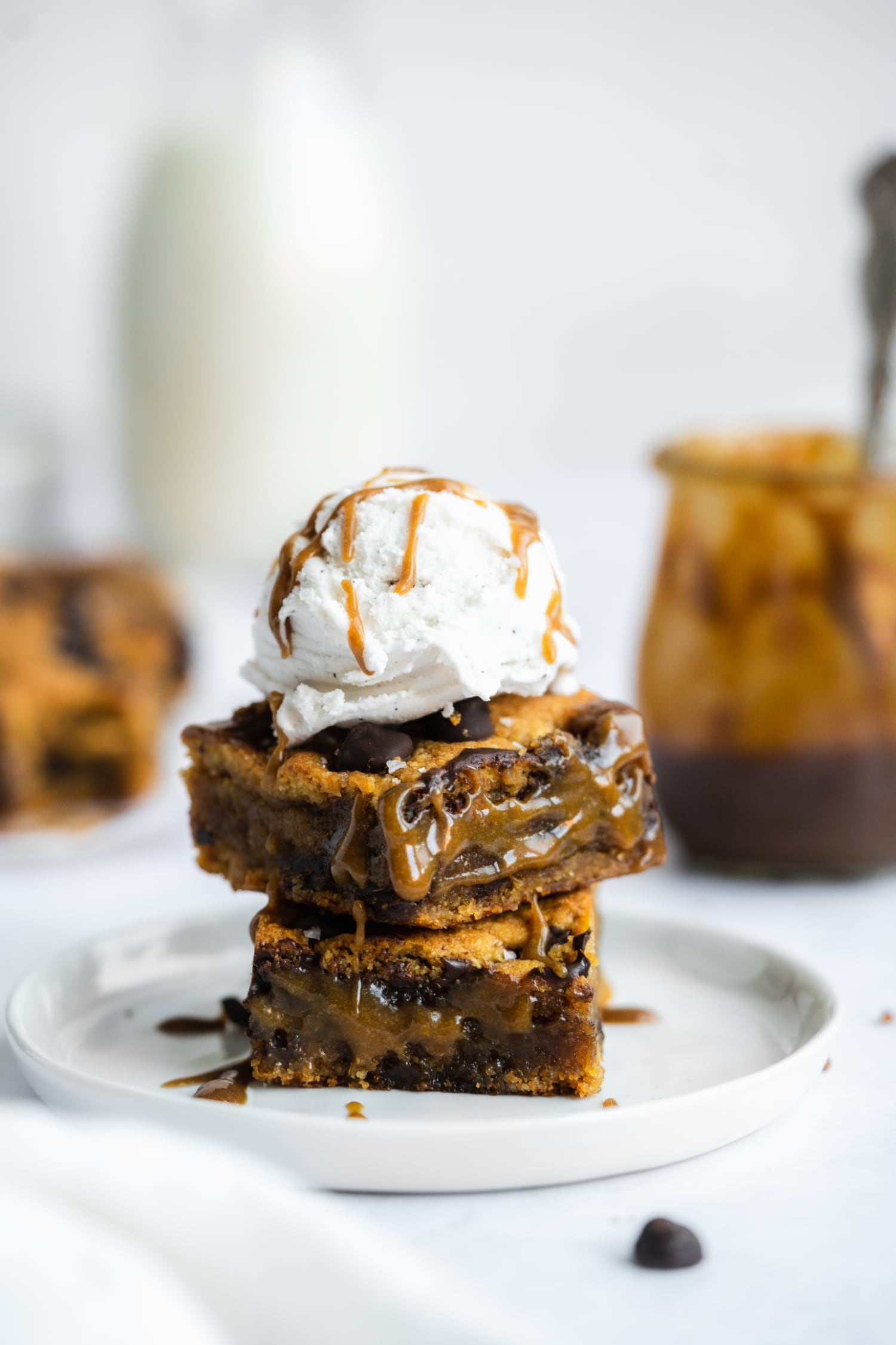 three salted caramel cookie bars stacked with ice cream on top