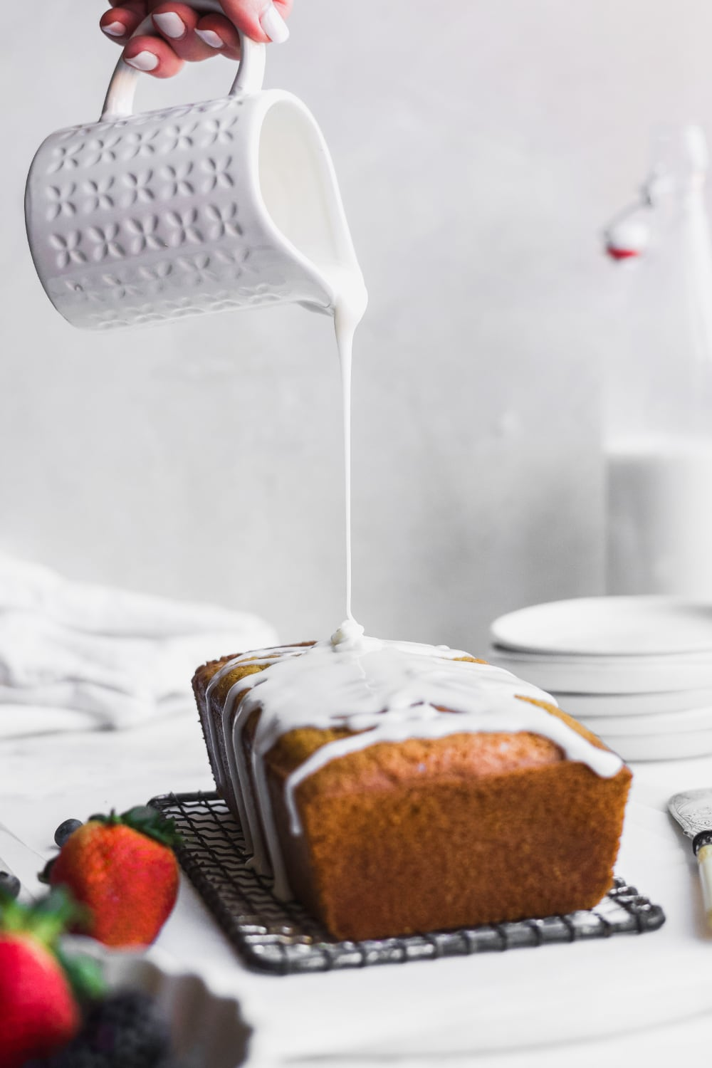 whole pound cake with vanilla icing being poured overtop